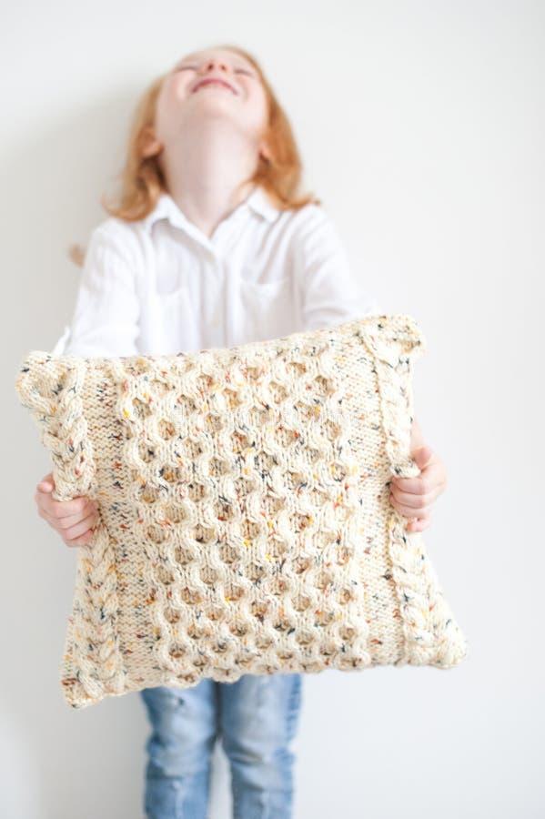 Flicka som rymmer en virkad kudde royaltyfria bilder