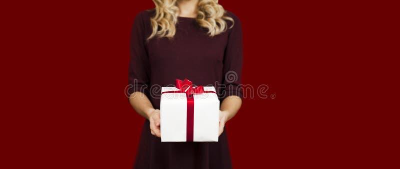 Flicka som rymmer en vit gåva med en röd pilbågenärbild på en röd bakgrund Begrepp för dag för valentin` s fotografering för bildbyråer