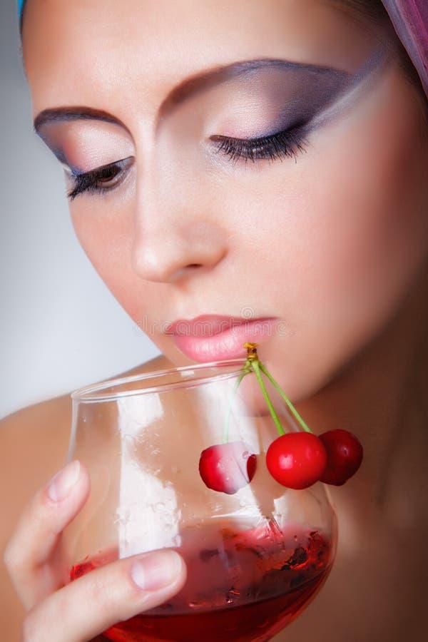 Flicka som rymmer ett exponeringsglas av rött vin arkivfoto