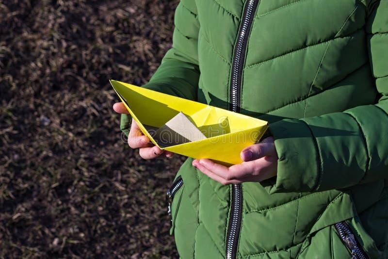 Flicka som rymmer ett gult pappers- fartyg, pappers- fartyg för närbild, arkivfoto