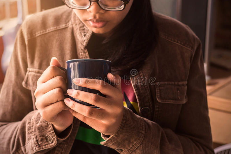 Flicka som rymmer ett kaffe på arbete arkivfoto