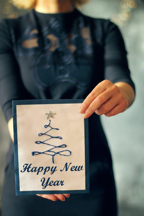 Flicka som rymmer ett kort för julträd främst av henne, täckt framsida royaltyfri fotografi