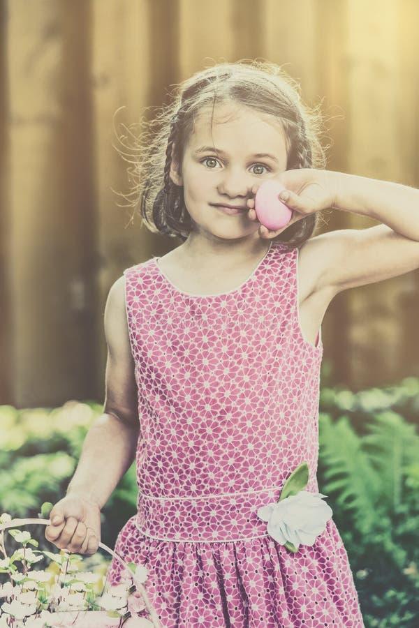 Flicka som rymmer ett rosa påskägg - Retro arkivfoto
