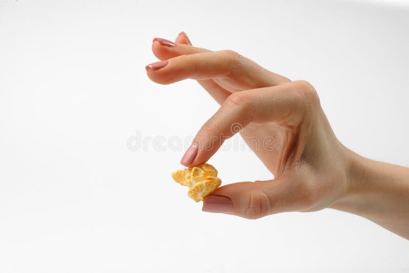 Flicka som rymmer ett ett stycke av ett läckert popcorn royaltyfri bild