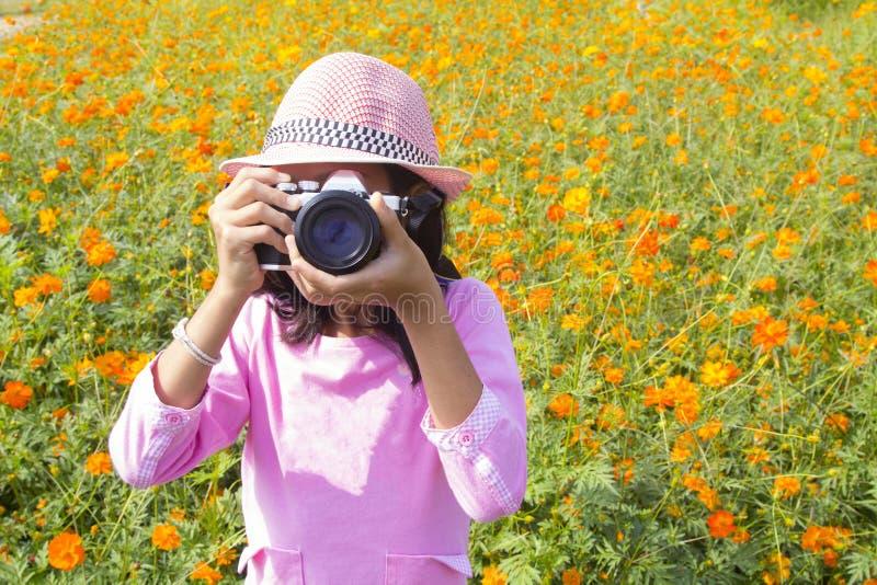 Flicka som rymmer kameran i blommaträdgård arkivfoton