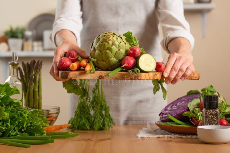 Flicka som rymmer nya grönsaker Begreppet av förlorande sund och hälsosam mat, detoxen, strikt vegetarian som äter, bantar och at arkivfoton