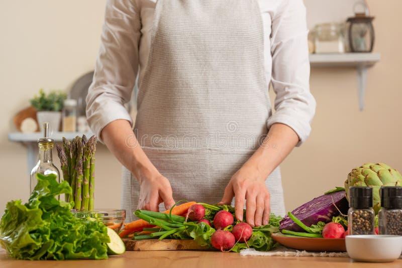 Flicka som rymmer nya grönsaker Begreppet av förlorande sund och hälsosam mat, detoxen, strikt vegetarian som äter, bantar och at arkivbilder