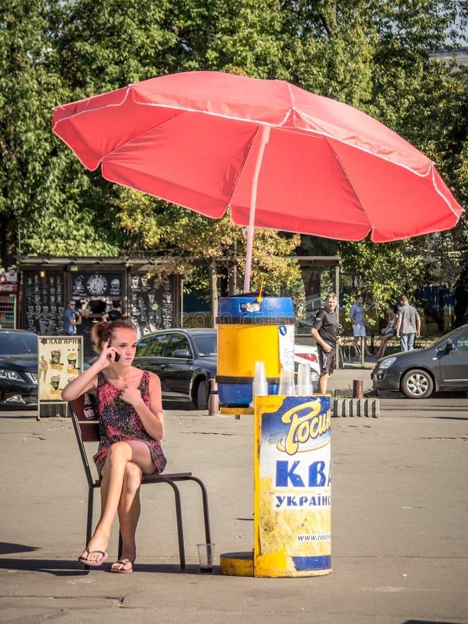 Flicka som säljer Kvass ett populärt östligt - europeisk drink som kontrollerar hennes smartphone på en gata av den ukrainska huv royaltyfri foto