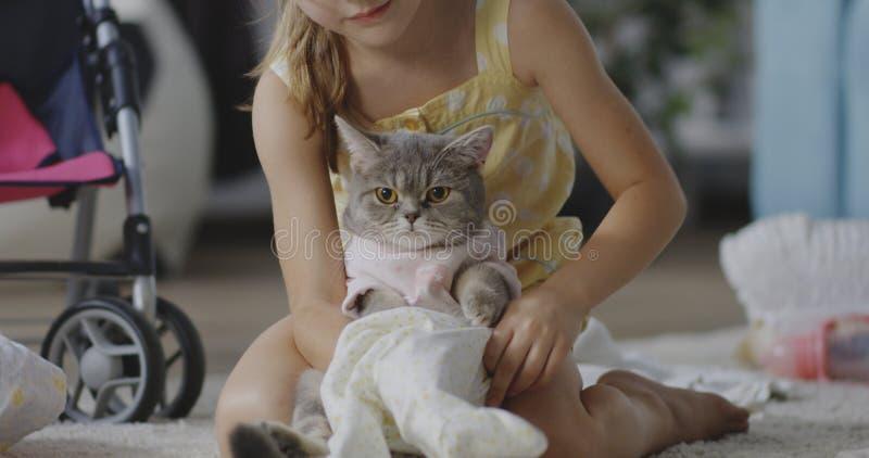 Flicka som sätter kläder på katt arkivfoton