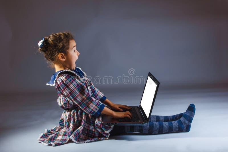 Flicka som ser datoren på en grå bakgrund arkivfoton