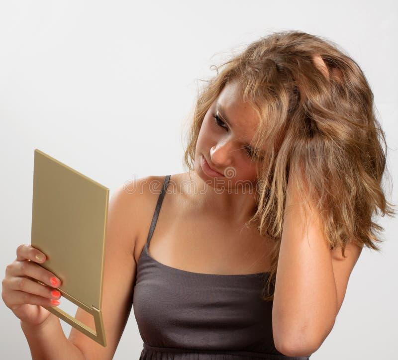 flicka som ser den teen spegeln royaltyfria bilder