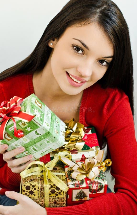 Flicka som ser det lyckliga innehavet många julklappar royaltyfri fotografi