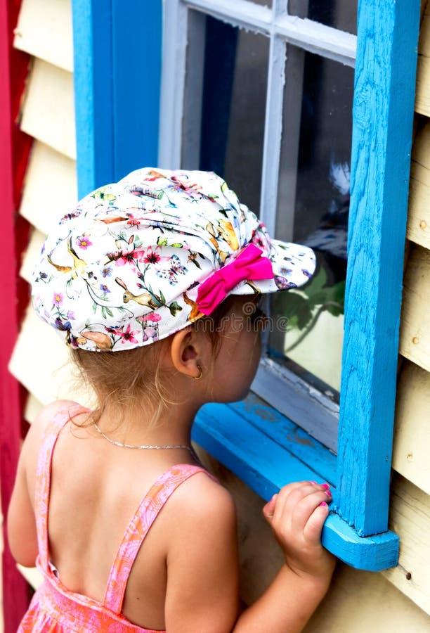 Flicka som ser fönstret. royaltyfria bilder
