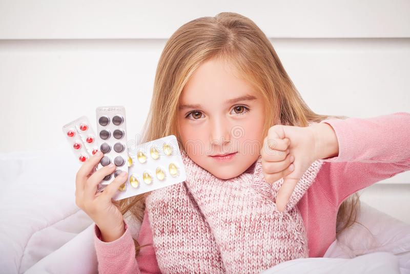 Flicka som ser förkylning- och influensapreventivpillerar arkivfoto