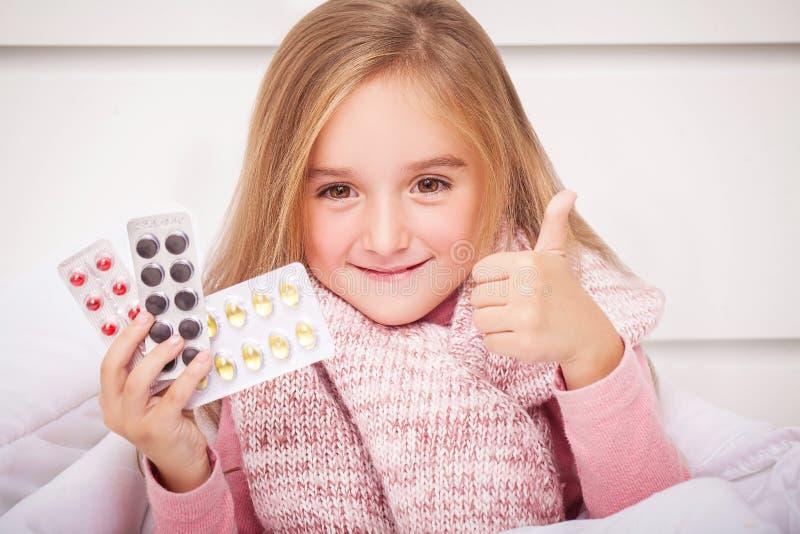 Flicka som ser förkylning- och influensapreventivpillerar arkivbilder