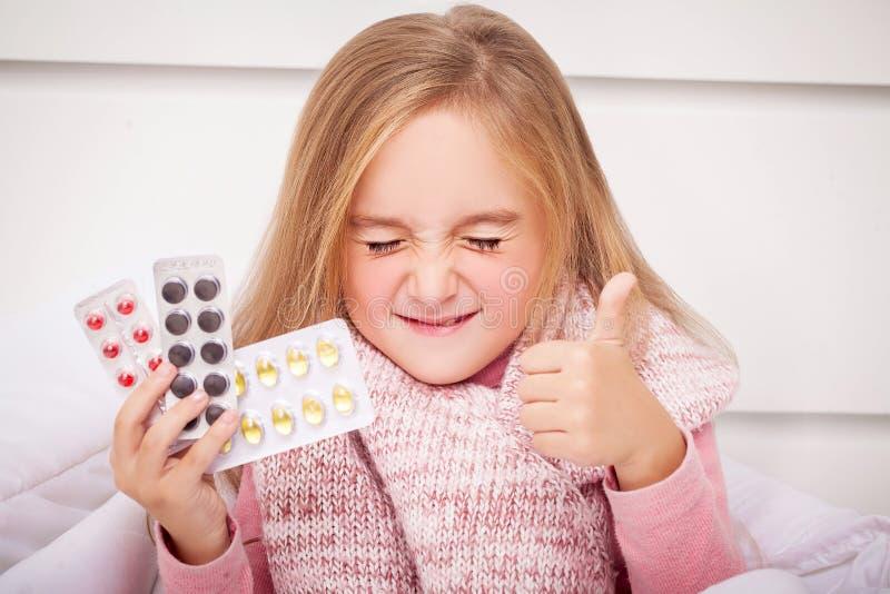 Flicka som ser förkylning- och influensapreventivpillerar arkivbild