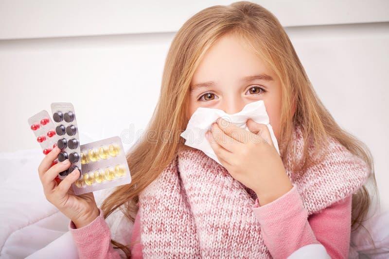 Flicka som ser förkylning- och influensapreventivpillerar fotografering för bildbyråer