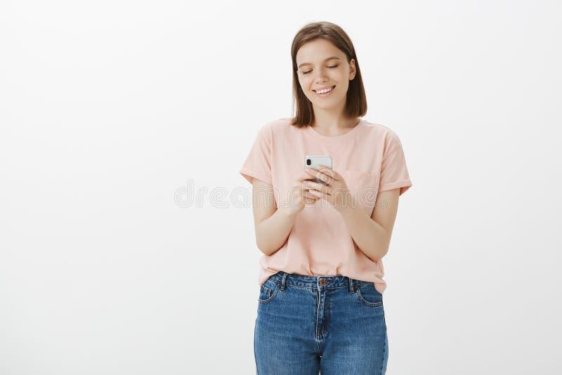 Flicka som ser fotoet av hennes älska hund medan på affärstur utomlands Lycklig charmig kvinna i tillfällig kläder som ler arkivbilder