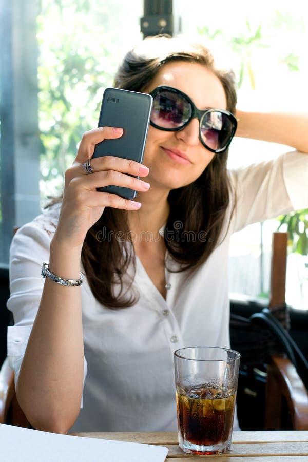 Flicka som ser hennes smartphone och tar en selfie med exponeringsglas - telekommunikationadvertizing royaltyfri bild