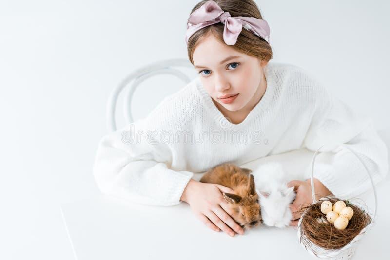 Flicka som ser kameran, medan sitta med päls- kaniner och korgen med easter ägg i rede på vit royaltyfri fotografi