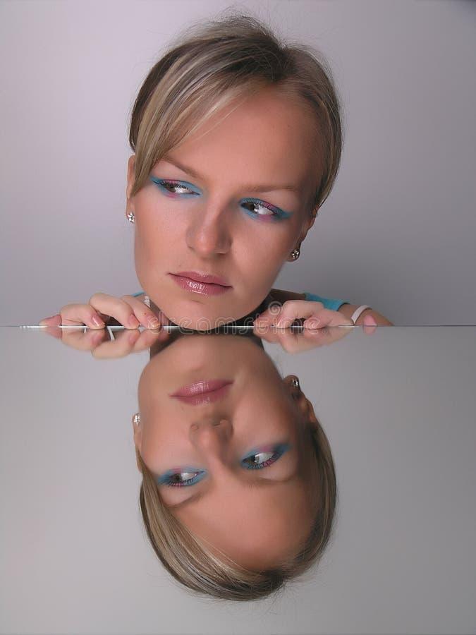 flicka som ser makeupspegeln royaltyfria bilder