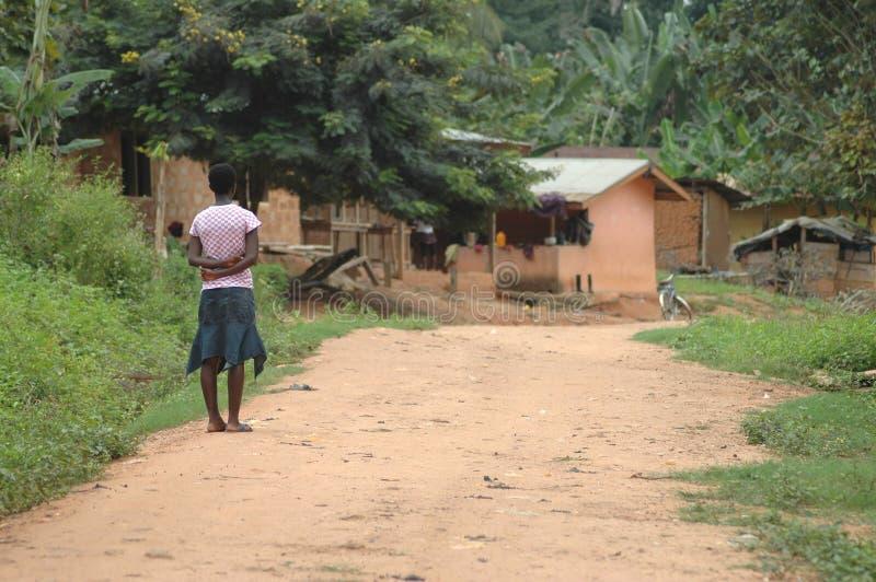 Flicka som ser ner grusvägen, Ghana royaltyfri fotografi