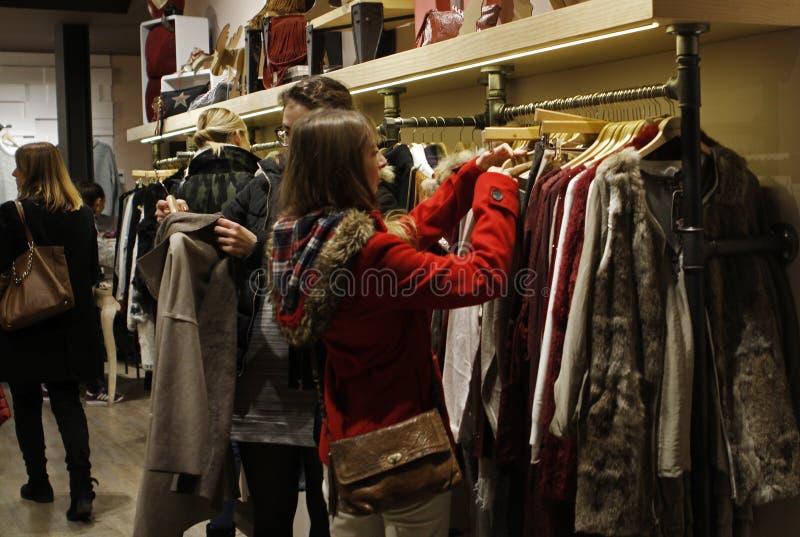 Flicka som ser omslag i ett klädlager arkivfoton