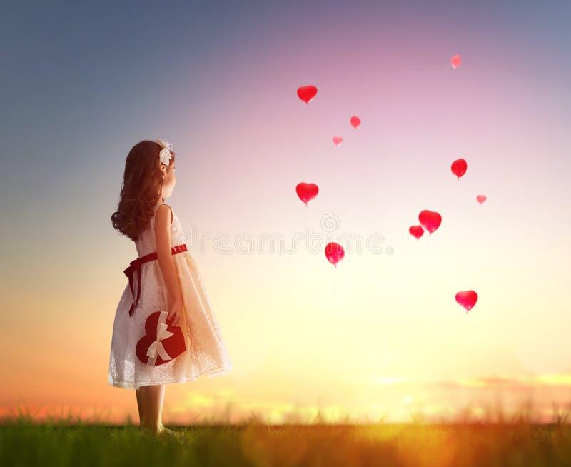 Flicka som ser röda ballonger royaltyfria foton