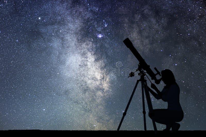 Flicka som ser stjärnorna med teleskopet Vintergatangalax royaltyfri fotografi