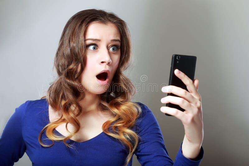Flicka som ser telefonen royaltyfri bild