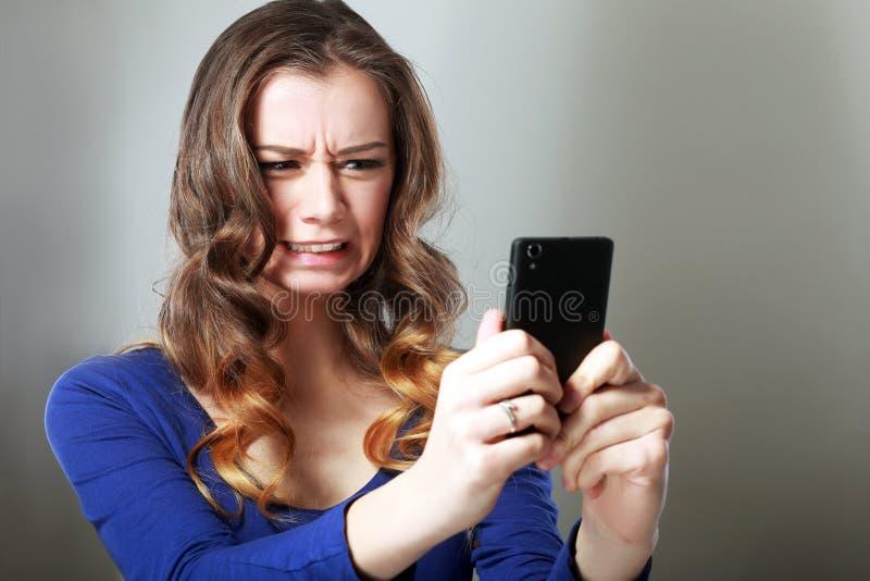 Flicka som ser telefonen royaltyfri foto