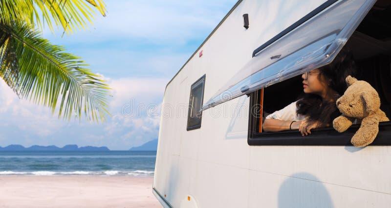 Flicka som ser ut ur fönster för campareskåpbil på sommarstranden royaltyfri foto