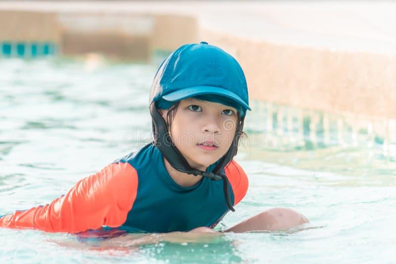 Flicka som siiting i en simbassäng royaltyfria bilder