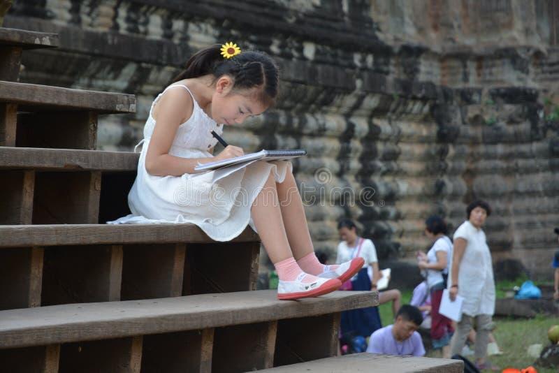 Flicka som sitter den utomhus- teckningsbilden arkivbilder