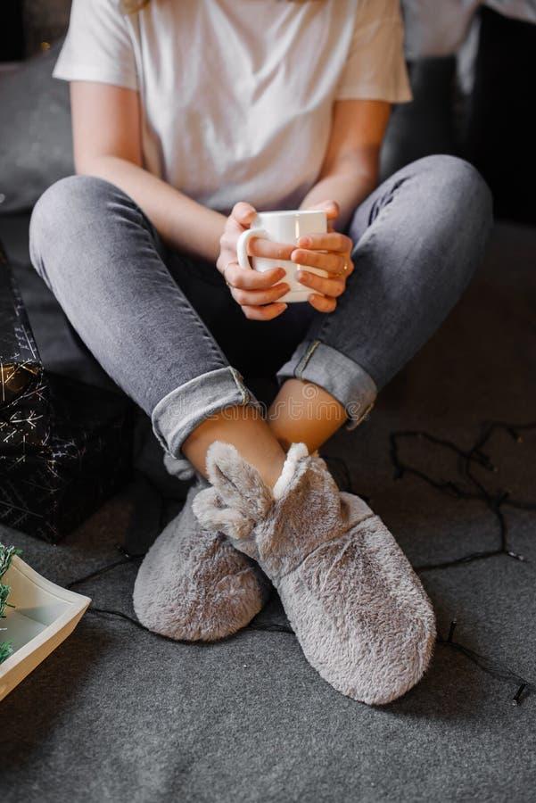 Flicka som sitter dricka varmt kaffe i ett vitt exponeringsglas arkivbilder