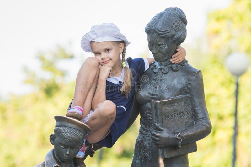 Flicka som sitter hänsynsfullt på monumentet till den första läraren arkivfoto