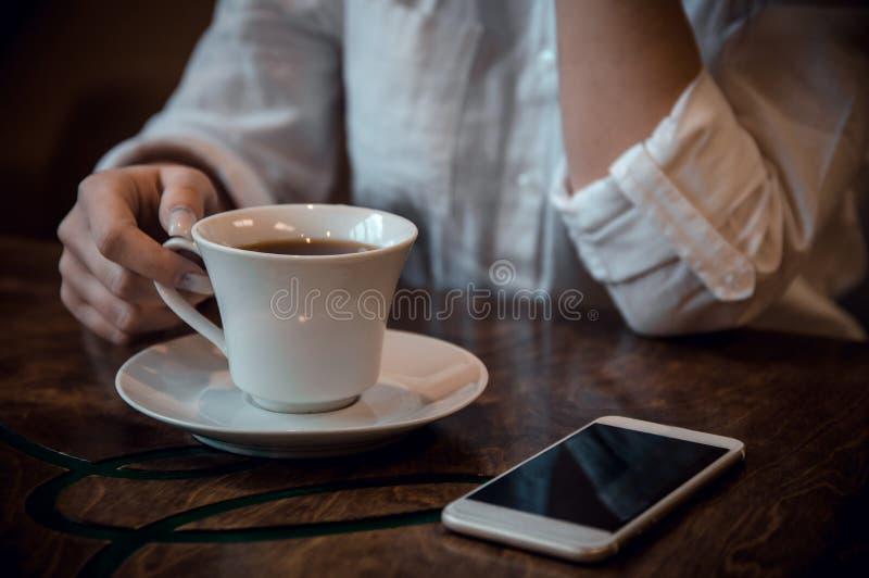 Flicka som sitter i ett kafé i en vit skjorta med en kopp kaffe och en telefon royaltyfri fotografi