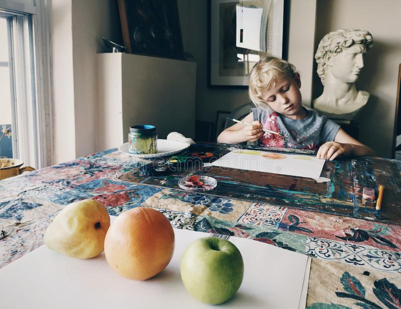 Flicka som sitter i hem- den koncentrerade konststudion på att måla frukter med borstar och vattenfärgmålarfärger arkivfoton