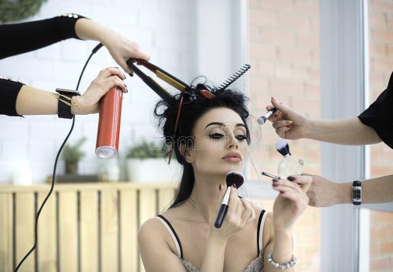 Flicka som sitter i underlag och applicerar makeup Två kvinnor hjälper henne royaltyfria bilder