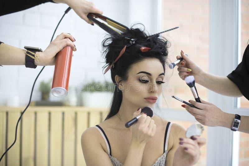 Flicka som sitter i underlag och applicerar makeup Två kvinnor hjälper henne royaltyfri foto