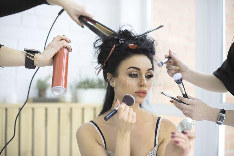 Flicka som sitter i underlag och applicerar makeup Två kvinnor hjälper henne arkivbild