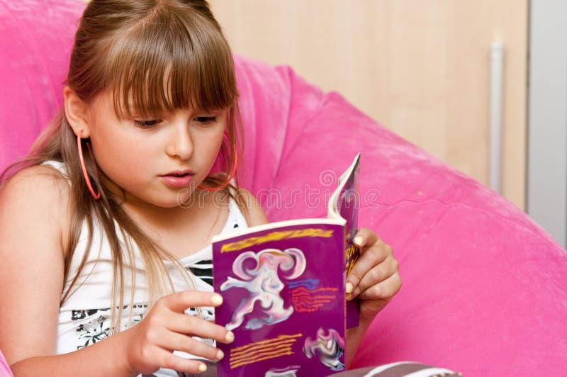Flicka som sitter läsa en bok royaltyfri foto