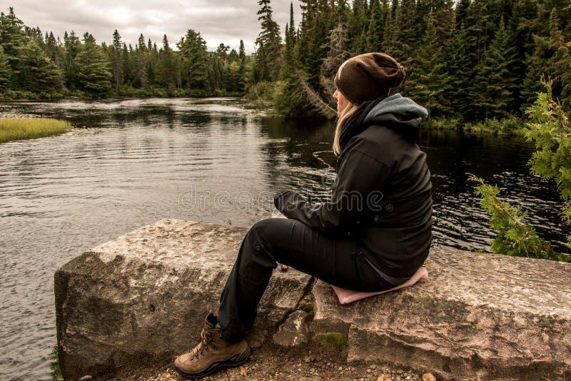 Flicka som sitter nära sjön av två floder i landskap för AlgonquinnationalparkKanada Ontario naturligt tall royaltyfri foto