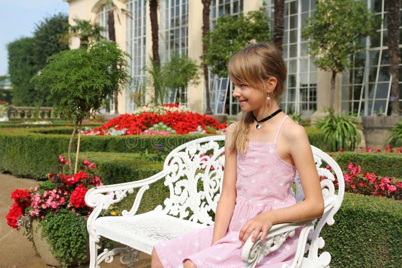 Flicka som sitter på bänk i trädgården arkivfoto
