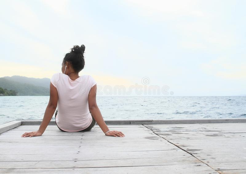 Flicka som sitter på bryggan vid havet royaltyfri bild