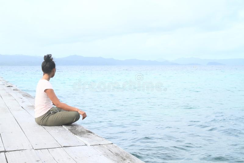 Flicka som sitter på bryggan vid havet royaltyfria foton