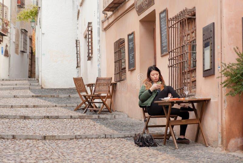 Flicka som sitter på det utomhus- kafét och håller ögonen på på telefonen med budbäraren arkivfoton