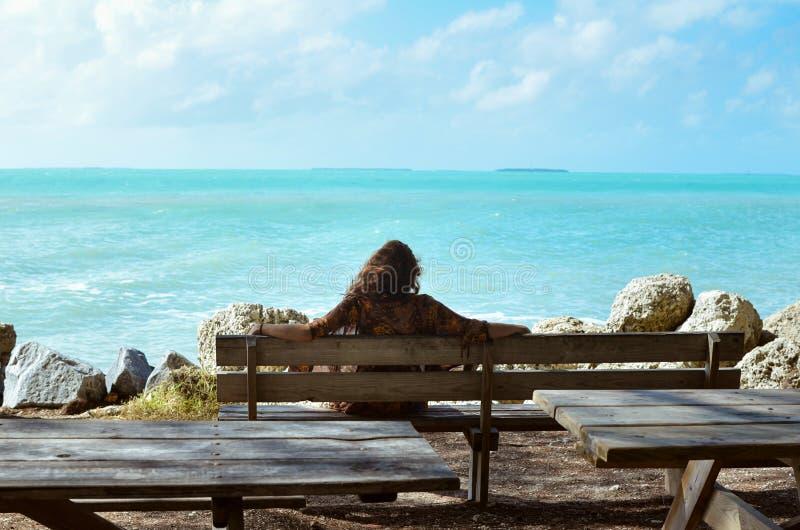 Flicka som sitter på en bänk bredvid havet royaltyfri bild