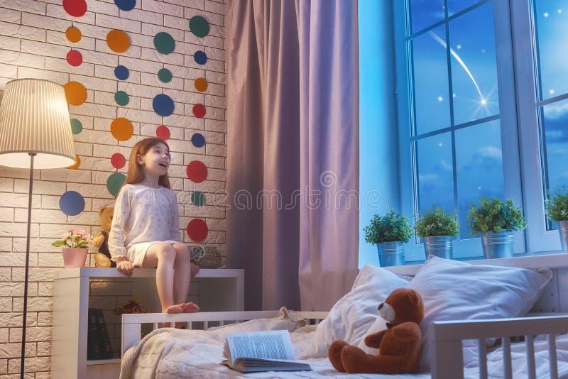 Flicka som sitter på fönstret royaltyfri foto