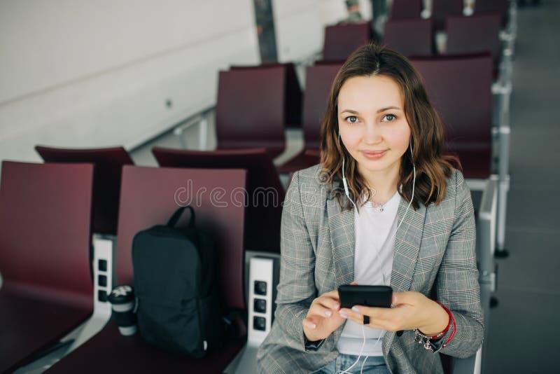 Flicka som sitter på flygplatsen som rymmer smartphonen royaltyfri foto
